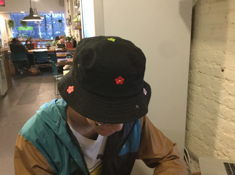 Taichi is sitting in a cafe, looking downward at his phone. He wears a black bucket hat sprinkled with embroidered flowers of various bright colors.